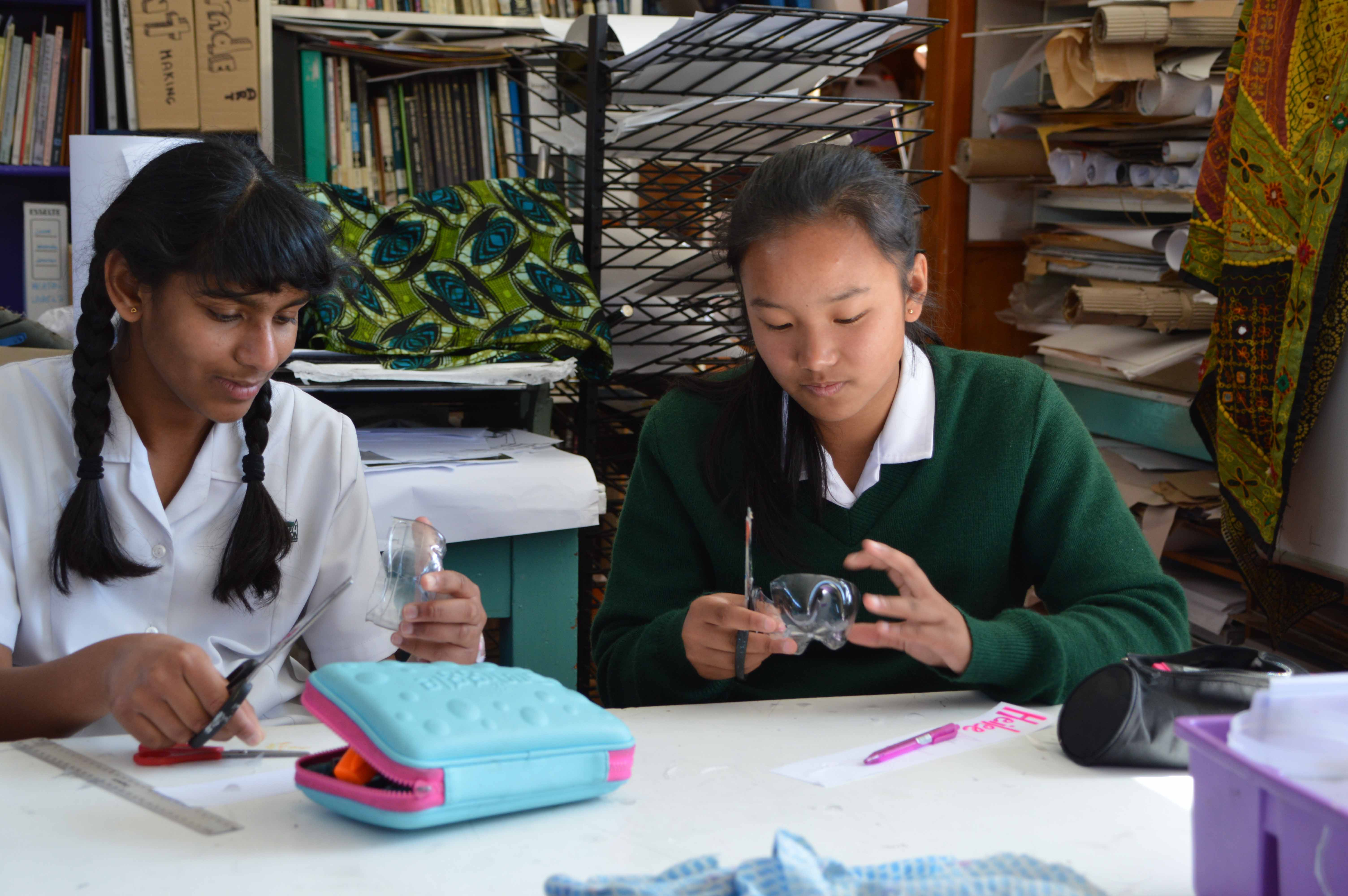 two Heaton Normal Intermediate School female students at a desk with pencil case and stationery